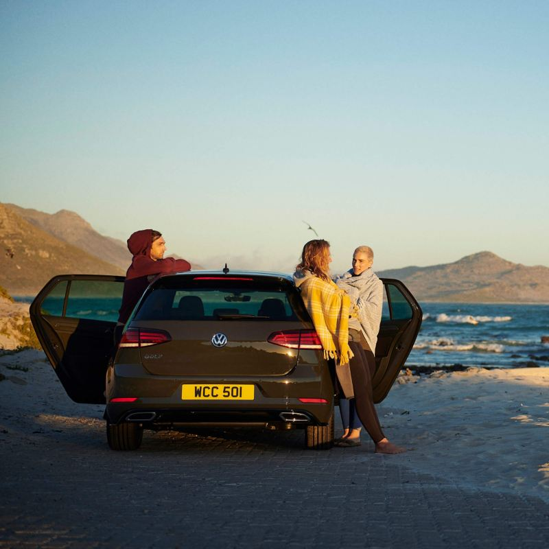 A group of young people with a Volkswagen Golf parked near the sea