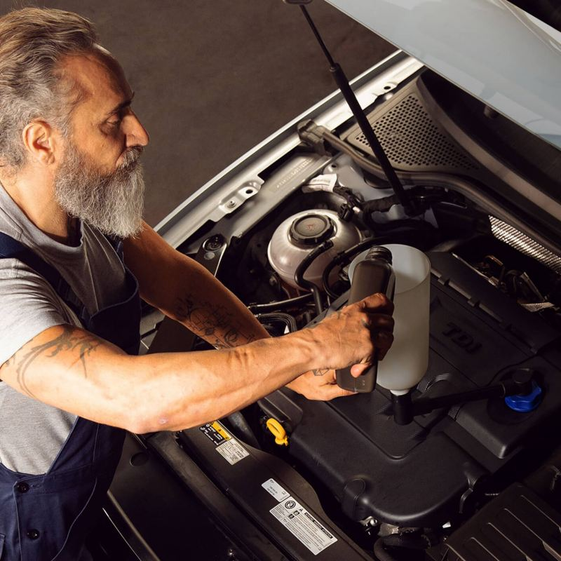 A VW service employee takes care of the right engine oil for your car