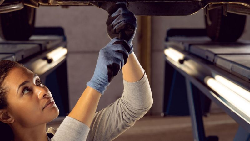 female mechanic changing engine oil