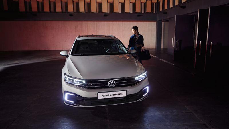 A woman entering a white Volkswagen Passat Estate GTE electric car