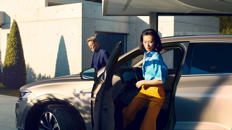 Man and woman stepping outside Volkswagen car