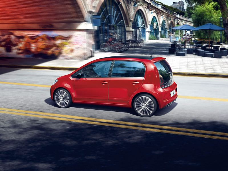Red Volkswagen Up! Driving though a quiet European city street.
