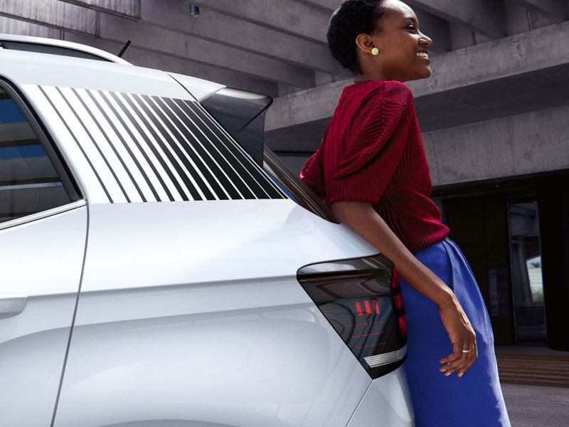Lady leaning against a Volkswagen car