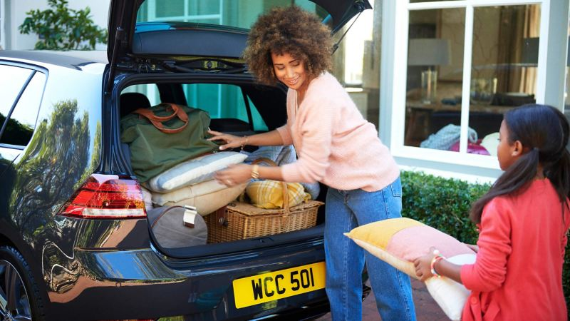 Family loading goods into the boot of a Volkswagen car