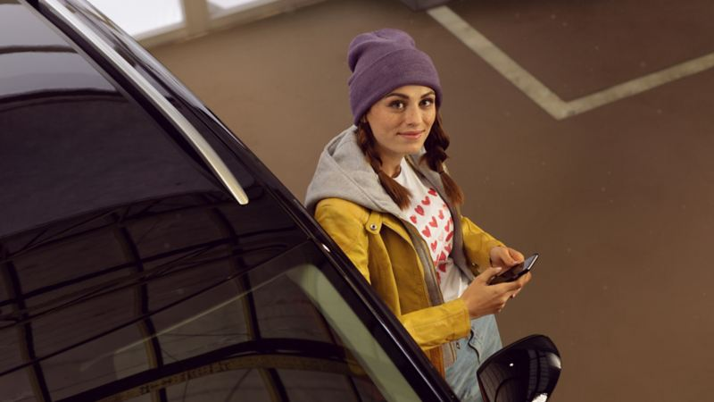 A smiling customer leaning on a Volkswagen car