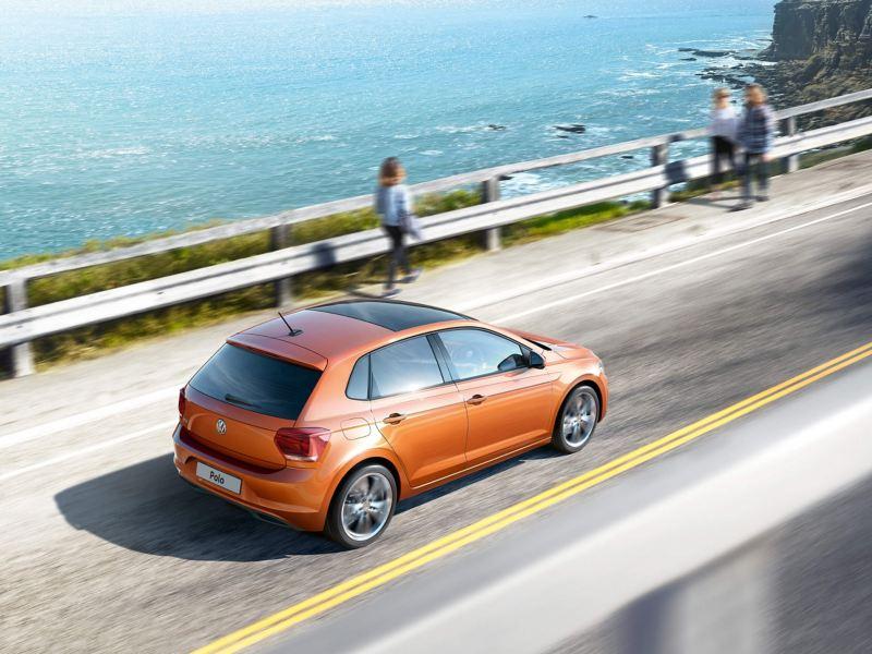 Orange Volkswagon Polo driving along a coastal road