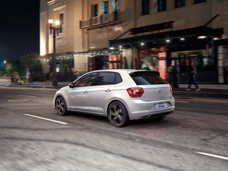 Silver Volkswagen R-Line driving through a city at night