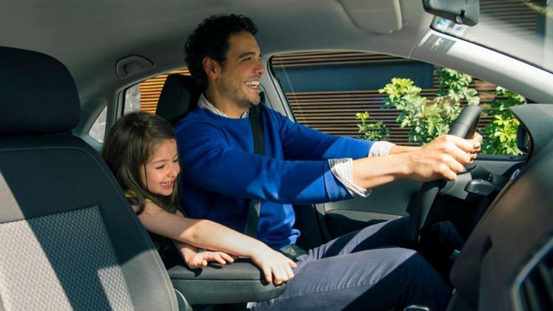 Interior de auto sedán de Volkswagen con padre e hija dando mantenimiento a carro durante contingencia