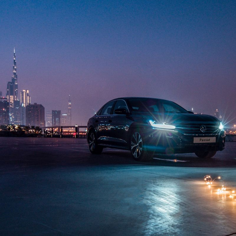 The 2020 Volkswagen Passat parked outside a city, a row of lights lay on the floor in front of it