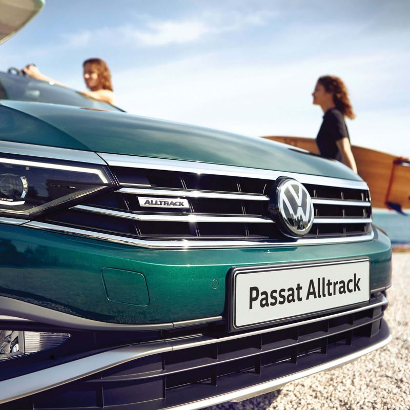 Front grill and badge shot of a green Volkswagen Passat Alltrack on a sandy beach.