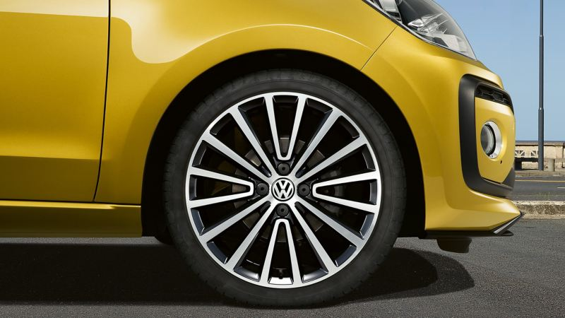 Front wheel shot of a yellow Volkswagen Golf.