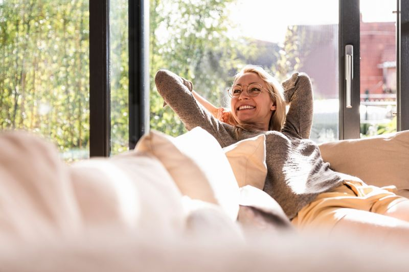 Lächelnde Frau zuhause auf ihrem Sofa.