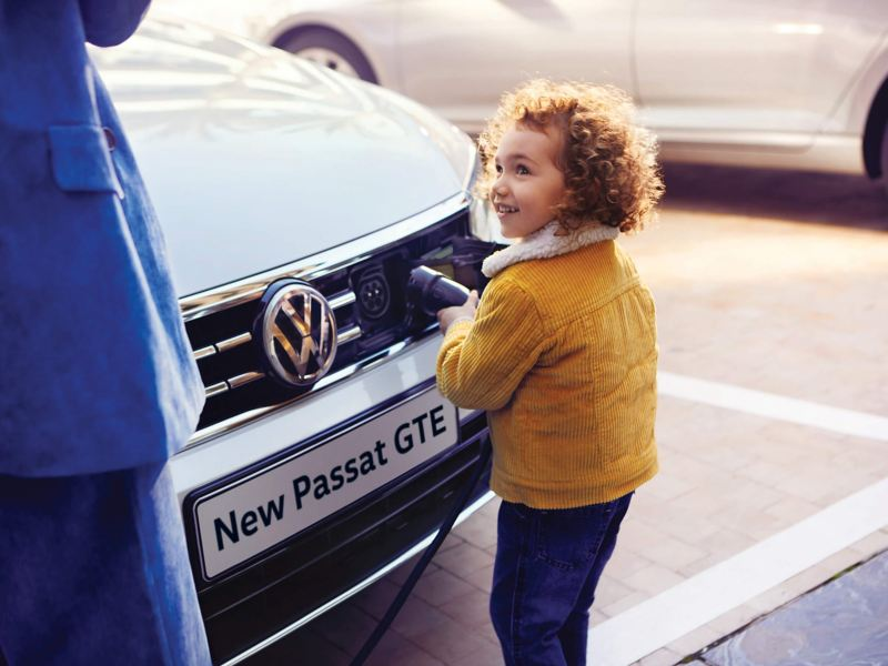 Young child plugging in the charger for a Volkswagon Passat GTE