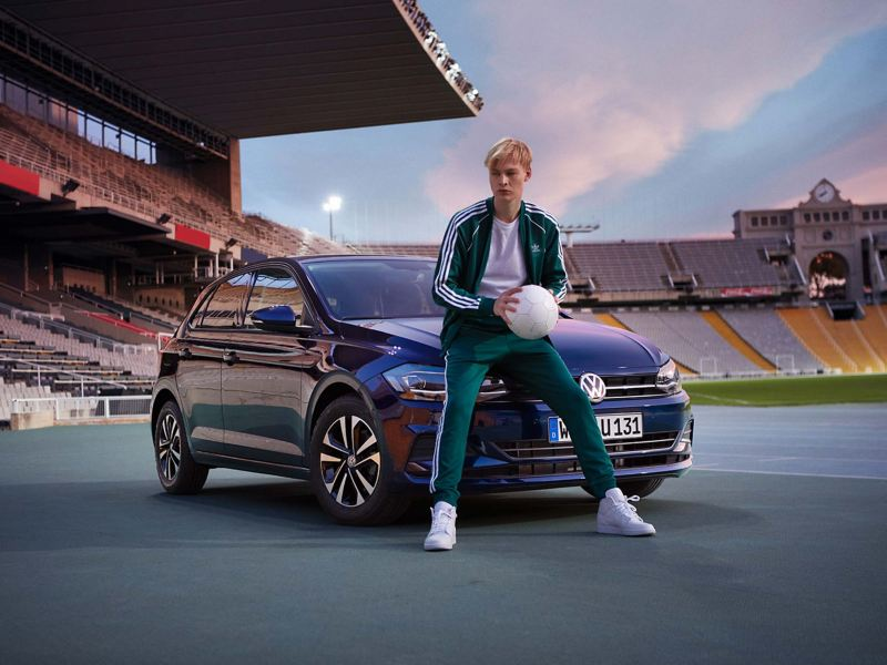 VW Polo UNITED in stadium, man posing in front of engine bonnet