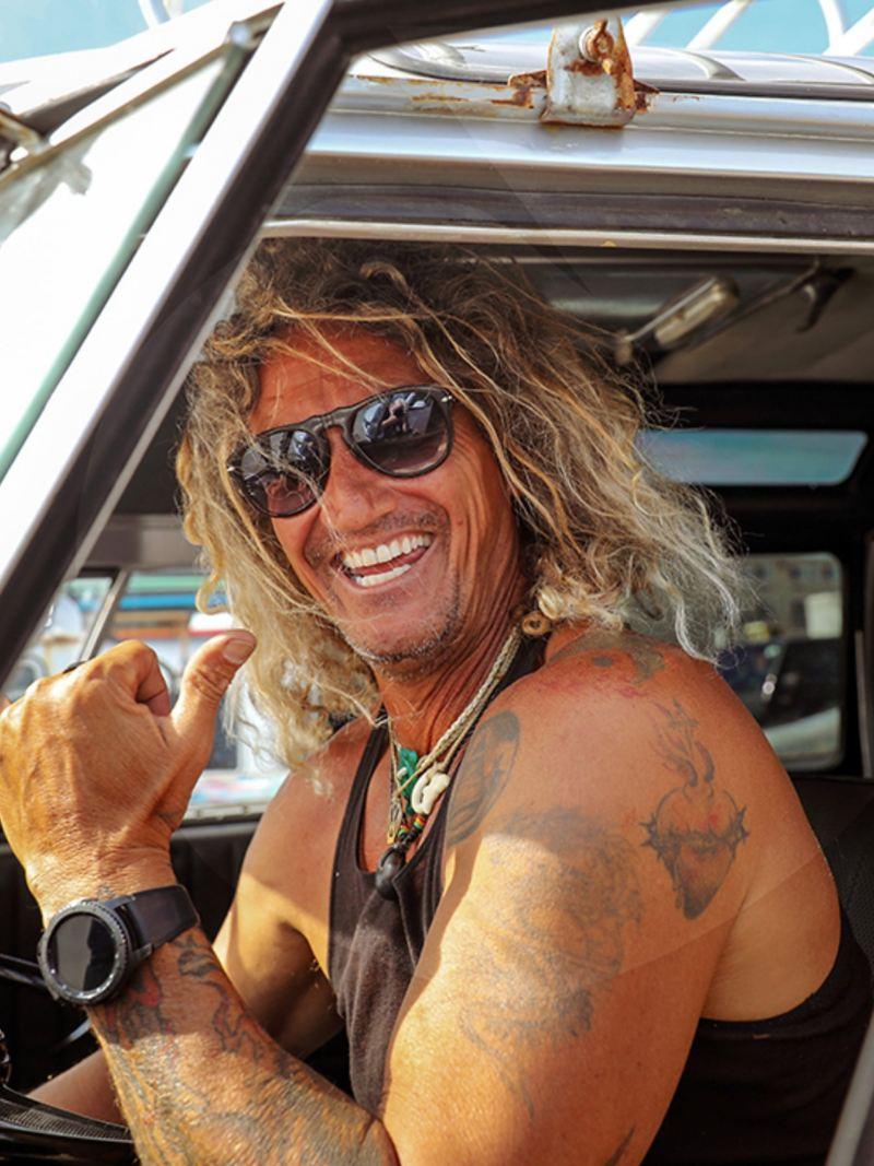 Surfer Martin sitzt am Steuer seines Californias und grüßt uns lächelnd.
