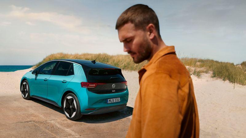 En man står framför en VW ID.3 på en sandstrand