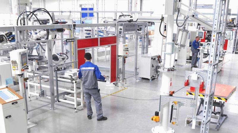 Zwei Volkswagen Mitarbeiter an ihren Arbeitsplätzen in einer Produktionshalle