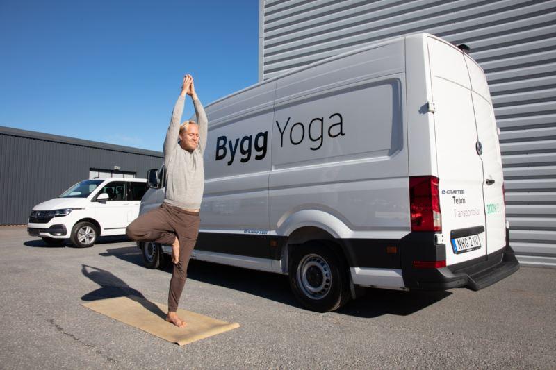 Person som gör yoga framför Volkswagen-bil