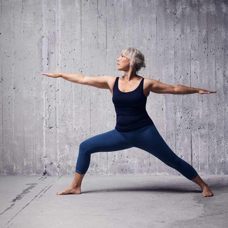 Kvinna gör Yoga mot en grå bakgrund