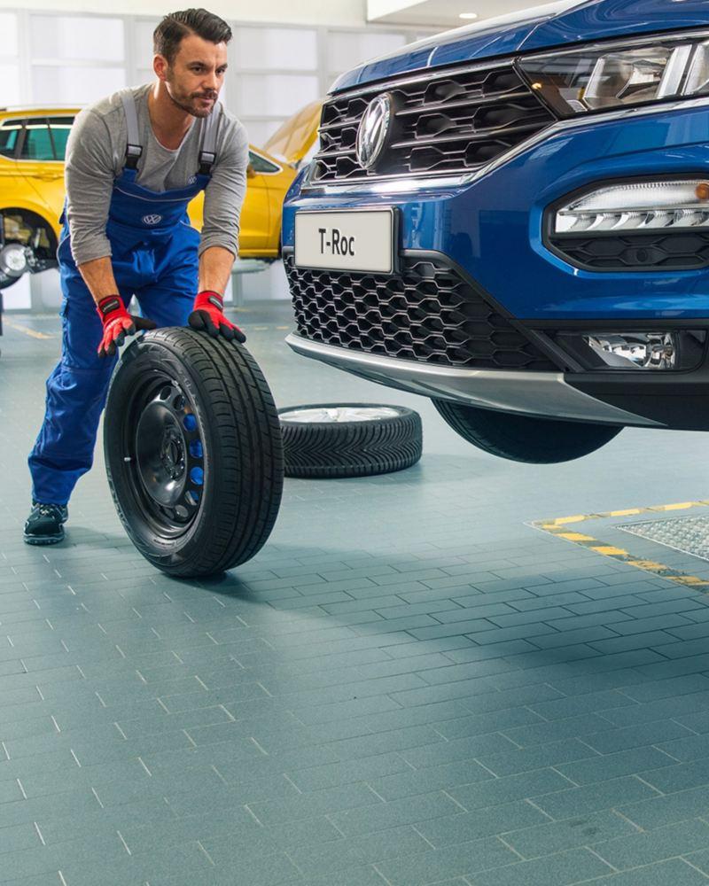 Meccanici Volkswagen Service montano gli pneumatici su una Volkswagen.