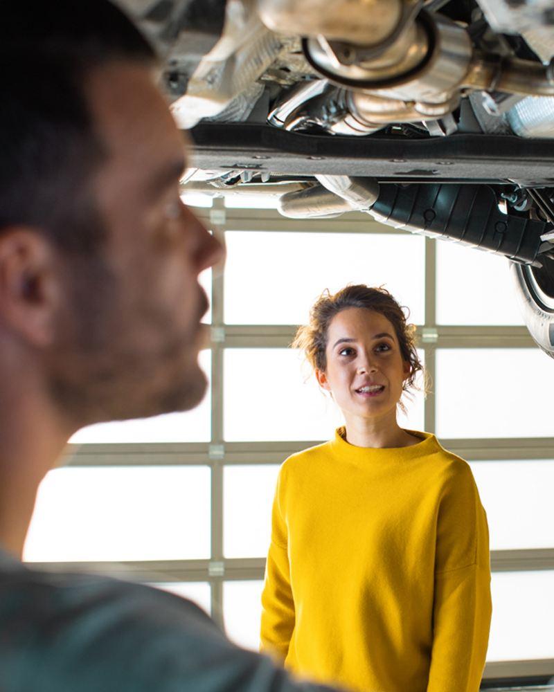 Donna parla con uomo che ispeziona sottoscocca auto Volkswagen sul ponte