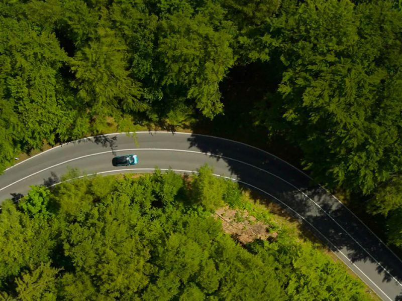 Way to Zero: VW ID.3 fährt durch einen grünen Wald. Vogelperspektive.