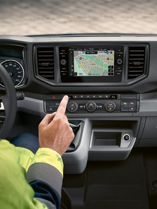 One hand operates the radio and navigation system in the cab of the Crafter.
