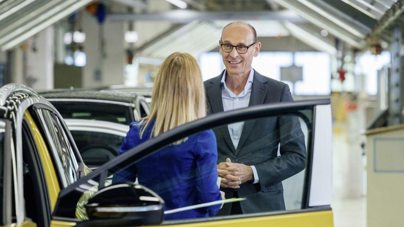 Ralf Brandstätter im Gespräch neben einem VW ID.4