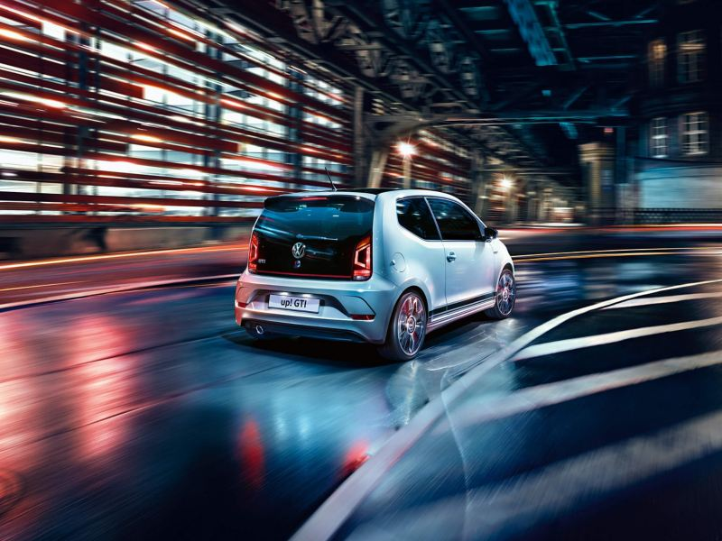 Rear view of a white Volkswagen e-up! driving on a dark city road.