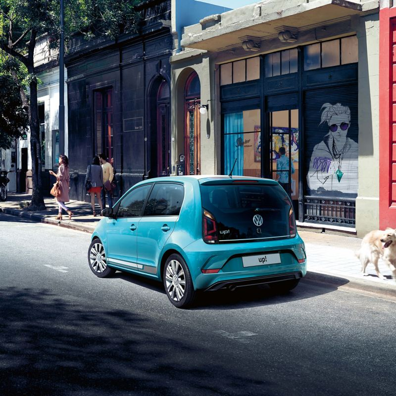A green Volkswagen up! parked on a shop-lined city road.