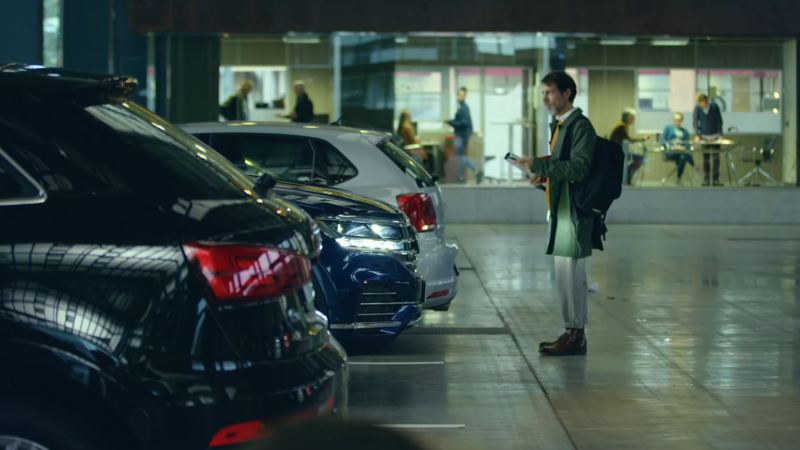 A man stands in a car park front of parked Volkswagen