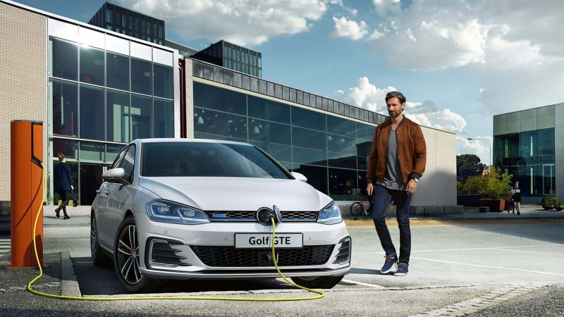 A man walking past a Golf GTE being charged