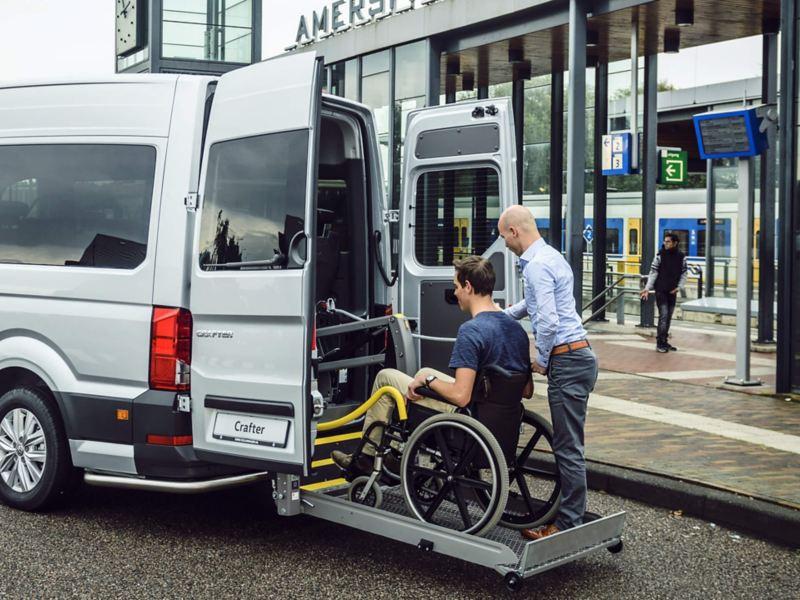 Passagier met rolstoel wordt in de Crafter Rolstoelvervoer geholpen.