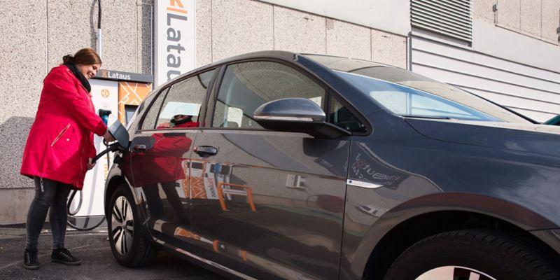Kuva henkilöstä lataamassa Volkswagenin sähköautoa latauspisteellä
