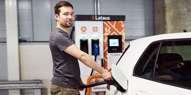 Kuva henkilöstä lataamassa sähköistä Volkswagen autoa