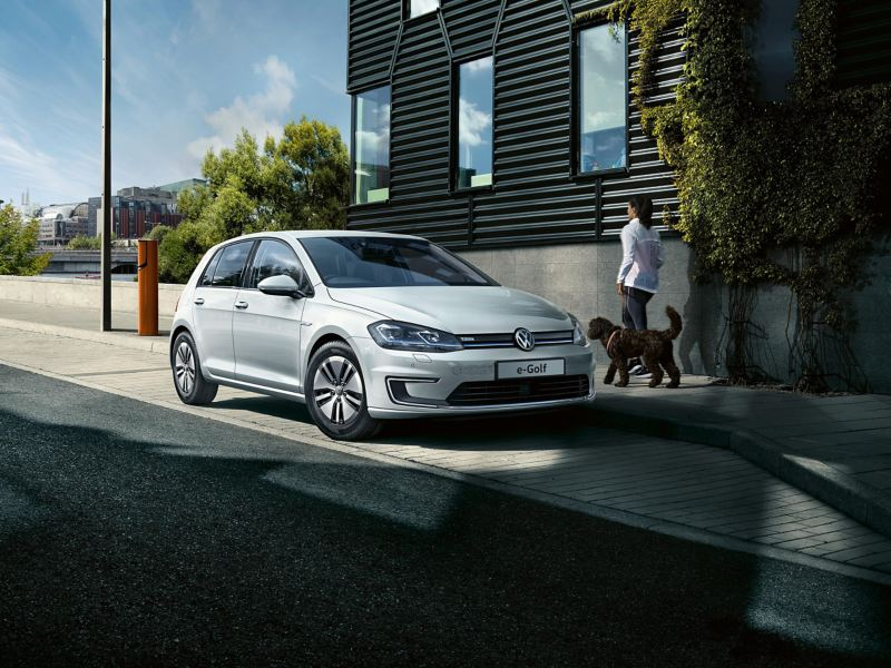 An e-Golf parked on a road and a woman walking a dog