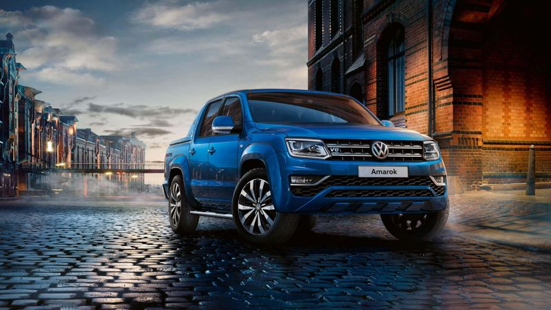 Blue Amarok VW van against city setting