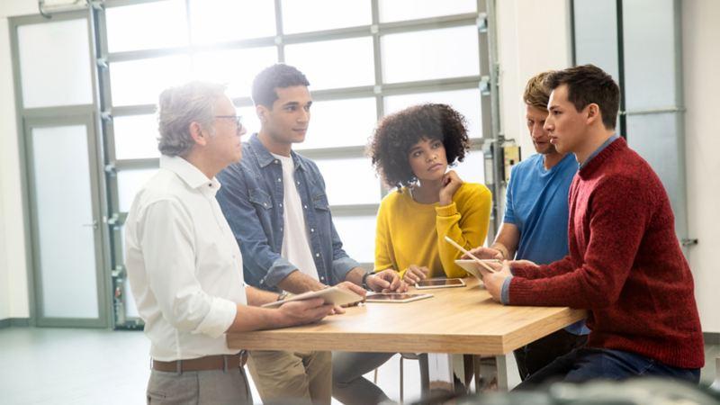 Fünf Geschäftsleute unterhalten sich an einem Tisch