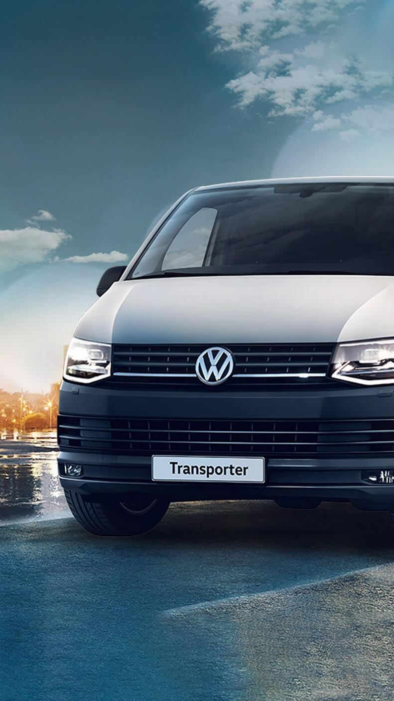 VW Transporter on wet street with city landscape