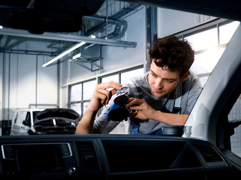 Mechanic fixiing windscreen on van