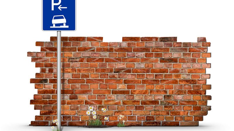 Road sign in front of brick wall
