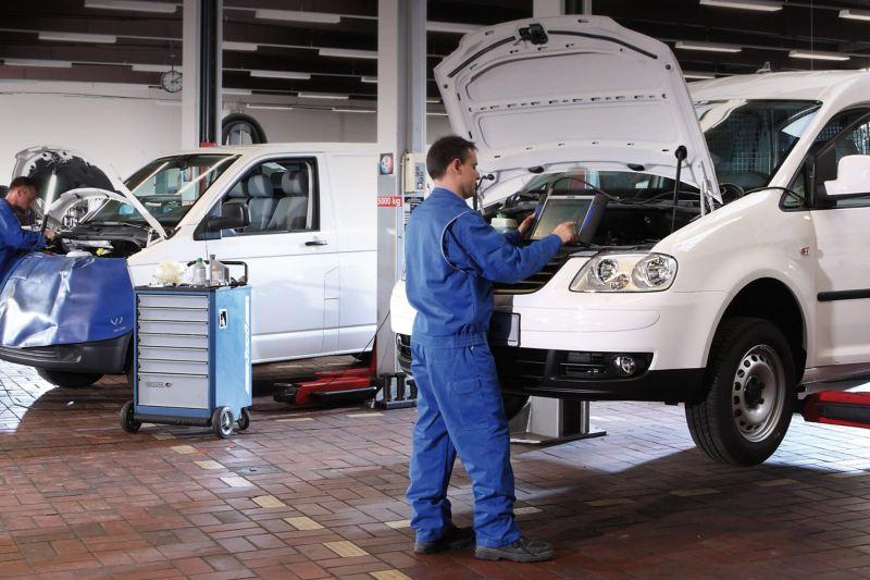 Volkswagen van specialist using diagnostic equipment under hood of van