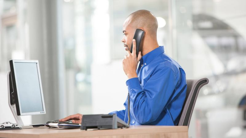 Man sat at desk on the phone, looking at his computer screen