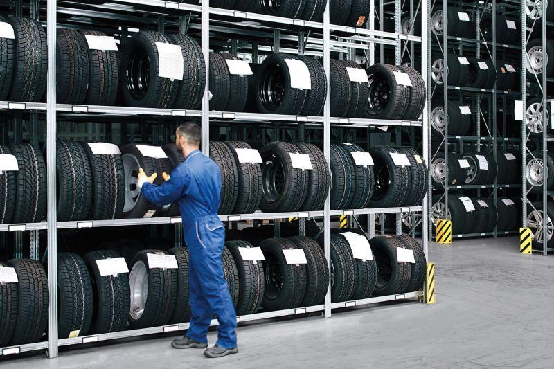 Mechanic taking tyres off shelf