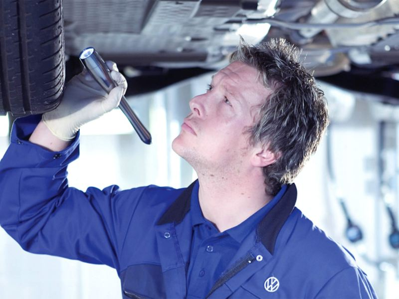 Technician working on the underside of a vehicle