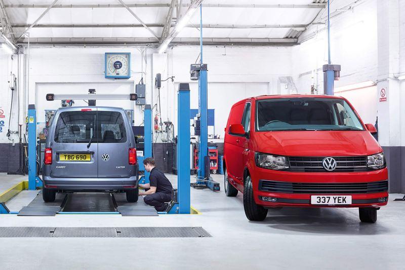 VW vans in garage being inspected by mechanic