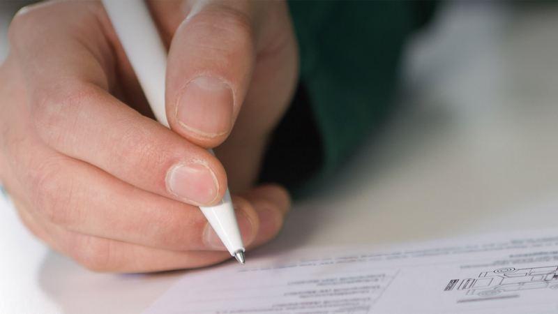 Dealer in VW Van Centre signing warranty sheet