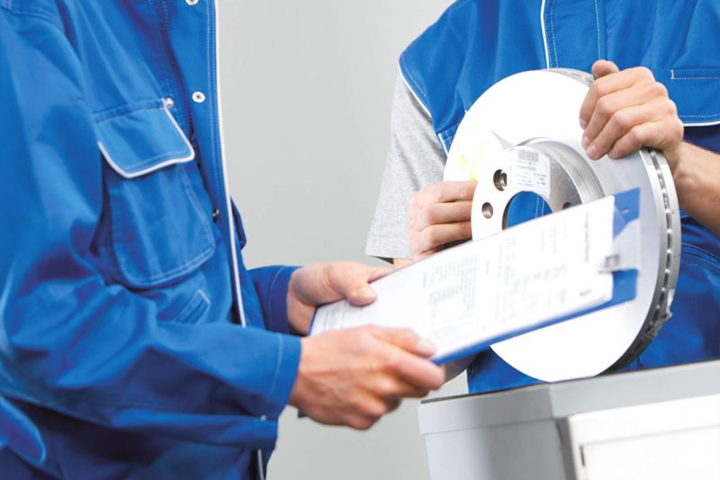 Technicians in VW Van Centre checking brake disc