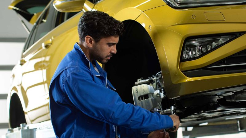 A service employee working on a Volkswagen car