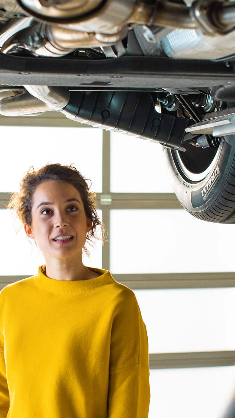 male mechanic fixing vehicle for while female customer watches